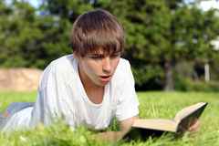 Surprised Teenager With a Book. Surprised Teenager lying on the Grass and reads a Book in the Summer Park Royalty Free Stock Image
