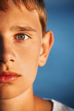 Surprised teenager boy against sea, half of face Stock Photo