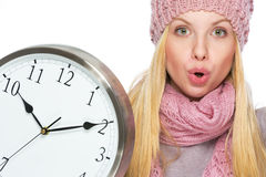 Surprised teenager girl in winter hat and scarf with clock Stock Photo