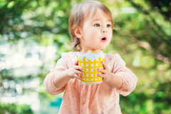 Surprised toddler girl playing outside Stock Image