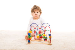 Surprised toddler with wooden toy Stock Photography