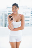 Surprised toned brunette holding smartphone Stock Photography