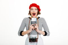 Surprised tourist lady with camera holding passport with tickets. Photo of young surprised tourist lady with camera isolated over white background wall holding stock photos
