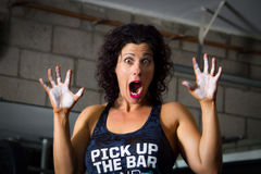 Surprised Trainer. A weight lifting trainer feigns surprise as she holds up chalky hands Stock Photos