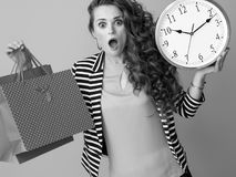 Surprised trendy woman showing clock and shopping bags Stock Image