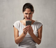 Surprised uncontented woman with smartphone Stock Photography