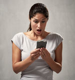 Surprised uncontented woman with smartphone Royalty Free Stock Image
