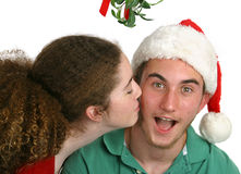 Surprised Under Mistletoe. A teen girl surprising a teen boy with a kiss under the mistletoe.  Isolated Stock Photo