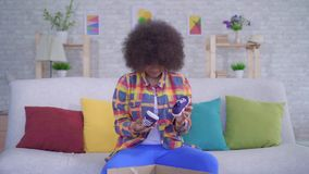 Surprised and upset african american woman with an afro hairstyle unpacks the parcel,wrong size stock video