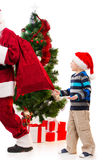 Surprised upset little boy watching Santa Clause leaving. Royalty Free Stock Photos