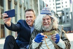 Elderly homeless vagrant feeling surprised after receiving money. Surprised vagrant. Elderly homeless vagrant feeling extremely surprised after receiving money royalty free stock image