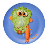Surprised vegetable ape made on blue plate. Ape made of cucumber, salad, carrot, onion and olives on blue plate. Photo shows how to make fun healthy food or royalty free stock photography