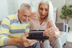 Surprised a vieilli des couples mettant leur téléphone intelligent à l'intérieur du dispositif de vr Photographie stock libre de droits