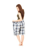 Surprised weight lost woman in too big pants Stock Photo