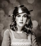 Surprised white housewife with colander on head. Portrait on background with bokeh. Image in black and white color style royalty free stock images