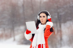 Surprised Winter Girl with Headphones and PC Tablet Royalty Free Stock Photos