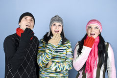 Surprised winter people looking up. Surprised and happy people friends looking up at copy space and having a surprise and holding their hands to mouth and Royalty Free Stock Photo