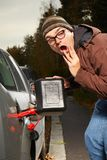 Surprised winter time dressed man filling tank of car Royalty Free Stock Photography