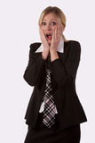 Surprised Woman. Blond woman wearing a black blazer and tie over white with hands on face with a shocked expression royalty free stock photo