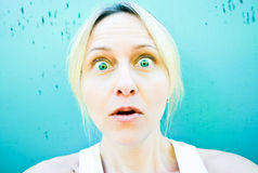 Surprised Woman. A surprised woman with green eyes against a aqua grungy background Stock Photography
