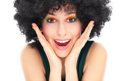 Surprised woman with afro wig. Woman wearing wig over white background Royalty Free Stock Image
