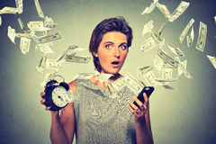 Surprised woman with alarm clock smart phone and dollar banknotes flying away. Online income business concept Royalty Free Stock Photography