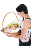 Surprised woman with baby found in basket Royalty Free Stock Photo