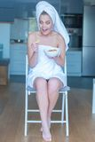 Surprised Woman in Bath Towel with Bowl of Snacks Royalty Free Stock Image