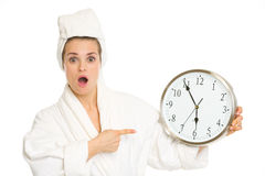 Surprised woman in bathrobe pointing on clock Royalty Free Stock Photography