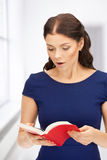 Surprised woman with book Stock Images