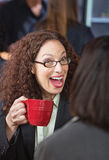 Surprised Woman in Cafe. Surprised woman laughing with friend in coffee house Stock Images