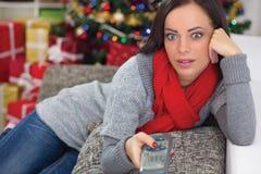 Surprised woman on Christmas night watching TV Stock Image