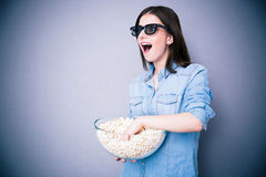 Surprised woman in cinema glasses holding bowl with popcorn Royalty Free Stock Images