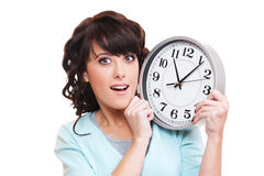 Surprised woman with clock. Portrait of surprised woman with clock over white background royalty free stock image