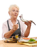 Surprised woman cooking trout Stock Images