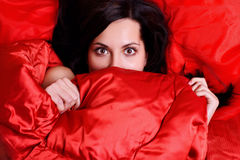 Surprised woman covered her face with a sheet Stock Photos