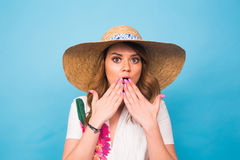 Surprised woman covering her mouth with hands over blue background with copy space and looking at camera.  Stock Photos