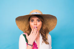 Surprised woman covering her mouth with hands over blue background with copy space and looking at camera Stock Photos