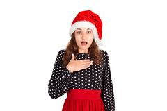 Surprised woman in dress holding hands on breast smiling being excited and shocked. emotional girl in santa claus christmas hat is royalty free stock photos