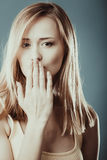 Surprised woman face covering her mouth with hand Stock Photo