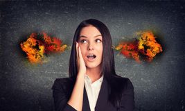 Surprised woman with fire from ears. Concrete gray Stock Photo