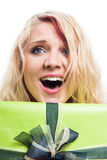 Surprised woman and gift. Closeup of surprised blond woman and green gift box, isolated on white background Stock Photography