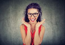 Surprised woman in glasses over gray background. Surprised young woman in glasses over gray grunge wall background Stock Images