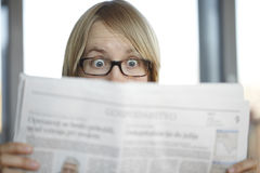 Surprised woman with glasses reading a newspaper Royalty Free Stock Photos