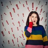 Exclamation shock. Surprised woman hand on her cheek holding mouth opened and exclamation marks like different thoughts escaping from head. Shock emotion concept stock photography