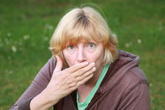 Surprised woman with hand over mouth Stock Images