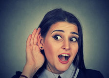 Surprised woman with hand to ear listening to gossip conversation Royalty Free Stock Photo