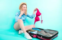Surprised woman has found that she has taken strange red brassiere. From the luggage. odd outfit royalty free stock photos