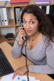 Surprised woman having a phone conversation sat at her desk Royalty Free Stock Photography