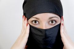 Surprised woman in hijab clutches her head Stock Images